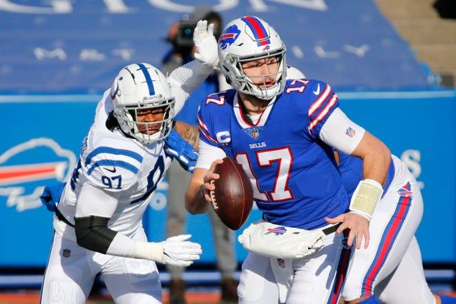 Bills quarterback Josh Allen (17) runs away from the Colts' Al-Quadin Muhammad during the first half Saturday at Orchard Park, New York.