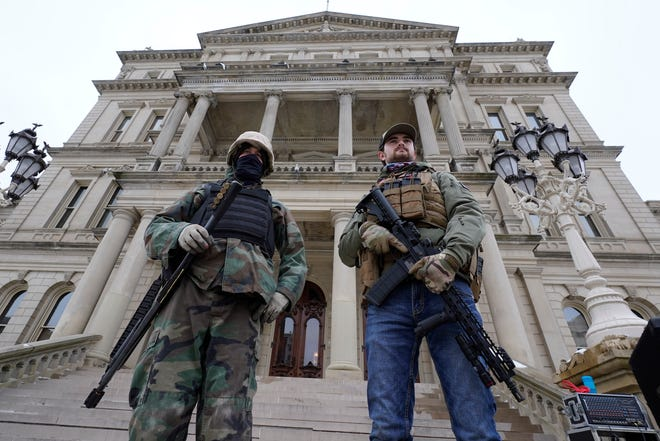 In this Jan. 6 file photo, armed men stand on the steps at the State Capitol after a rally in support of President Donald Trump in Lansing, Mich.