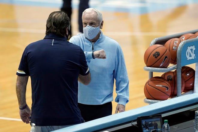 Notre Dame coach Mike Brey, left, and North Carolina coach Roy Williams greet each other prior to the game between their teams last weekend at the Smith Center.