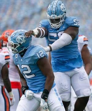 Tomari Fox, right, congratulates older brother Tomon Fox after the North Carolina defense delivered one of seven sacks against Syracuse in September.