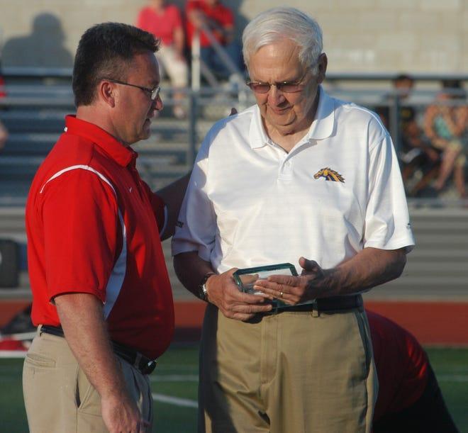 Retiring head football coach Bob Schneider (right) of Newport Central Catholic accepts an award from Beechwood head coach Noel Rash in 2010.
