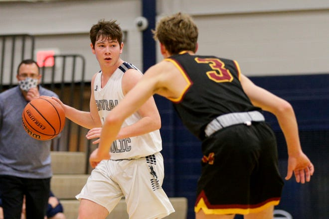 Central Catholic's Tanner Sterrett (14) dribbles against McCutcheon's Brock Dimmitt (3) during the second quarter of an IHSAA boys basketball game, Friday, Jan. 8, 2021 in Lafayette.