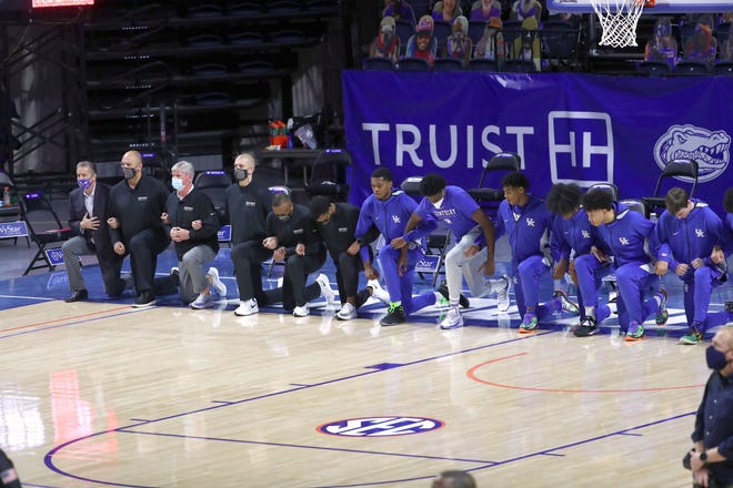 Jan 9, 2021; Gainesville, Florida, USA; Kentucky Wildcats coaches and players kneel during the national anthem prior to a game against the Florida Gators at Billy Donovan Court at Exactech Arena.