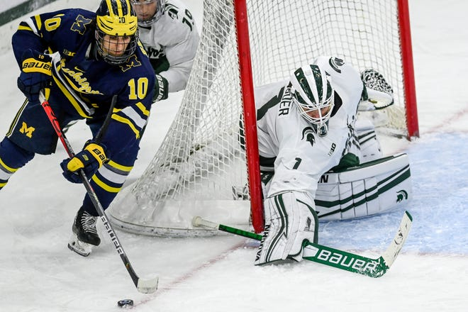 Michigan State's goalie Drew DeRidder, right, prepares to stop a shot by Michigan's Matty Beniers during the third period on Saturday, Jan. 9, 2021, at the Munn Ice Arena in East Lansing.