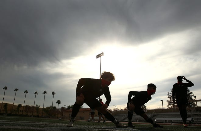 Jan 8, 2021; Phoenix, AZ, USA; Brophy Prep soccer players stretch at soccer practice after the Arizona Interscholastic Association Executive Board voted to cancel the high school winter sports season due to surging COVID-19 cases in Arizona. Mandatory Credit: Rob Schumacher-Arizona Republic