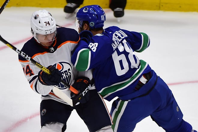 Sep 17, 2019; Vancouver, British Columbia, CAN; Vancouver Canucks forward Vincent Arseneau (68) checks Edmonton Oilers defenseman Ethan Bear (74) during the third period at Rogers Arena. Mandatory Credit: Anne-Marie Sorvin-USA TODAY Sports