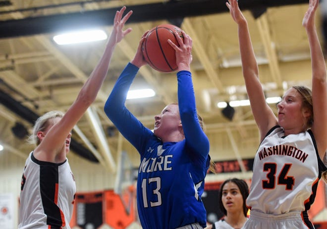 St. Thomas More's Haleigh Timmer goes up to the basket while being guarded by Washington players during their game on Friday, January 8, at Washington High School in Sioux Falls.