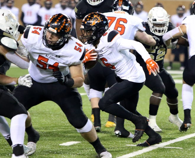 Aledo's Demarco Roberts rushes through the line of scrimmage against Rider last week in the Class 5A Division II state semifinal at Apogee Stadium in Denton. Roberts scored six rushing touchdowns in the state championship game on Friday afternoon to lead Aledo to a record 10th title.