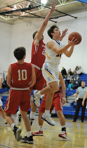 West Muskingum's Jack Porter drives past Sheridan's Ethan Malone in Friday's game at West Muskingum. The Tornadoes won 62-57.