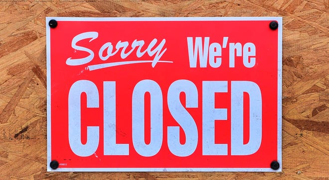 """A """"Closed"""" sign is seen amid the ccoronavirus pandemic in Los Angeles, California on December 5, 2020."""