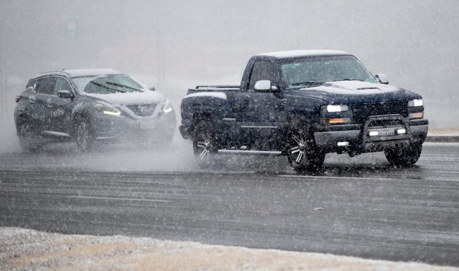 People drive in the snow on Research Boulevard on Sunday January 10, 2021.
