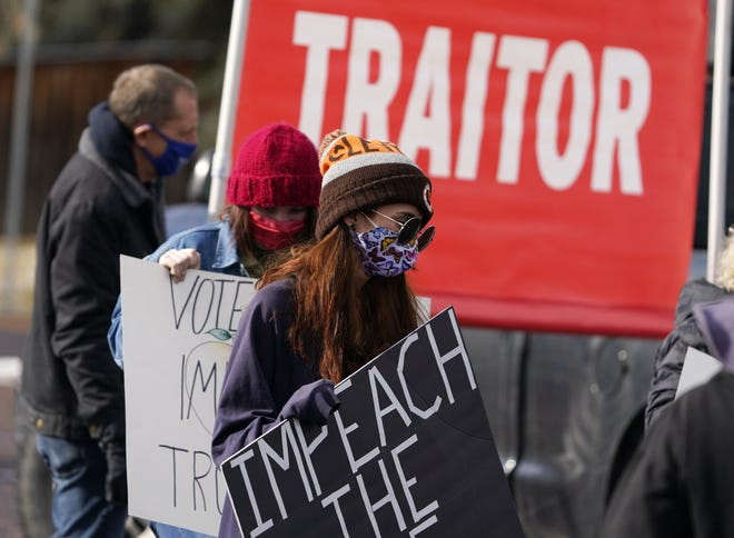People carry placards during a gathering calling for the impeachment of President Donald Trump in Denver on Sunday. [AP Photo/David Zalubowski]