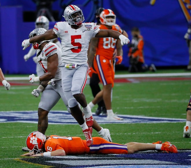 Ohio State linebacker Baron Browning celebrates a fourth-down stop as he leaps over Clemson quarterback Trevor Lawrence during the Buckeyes' 49-28 win in a College Football Playoff semifinal Jan. 1. Browning will be among 20 players on the field in Monday's national championship game who might be drafted in April.