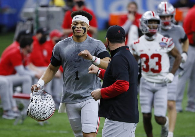 Ohio State quarterback Justin Fields gives a first bump to coach Ryan Day prior to the College Football Playoff semifinal against Clemson in New Orleans on Jan. 1.
