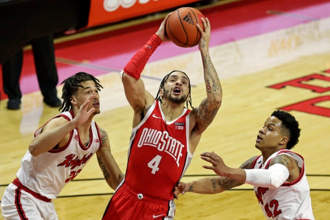 Ohio State guard Duane Washington Jr. drives to the basket between Rutgers guards Jacob Young, left, and Caleb McConnell during Saturday's game.