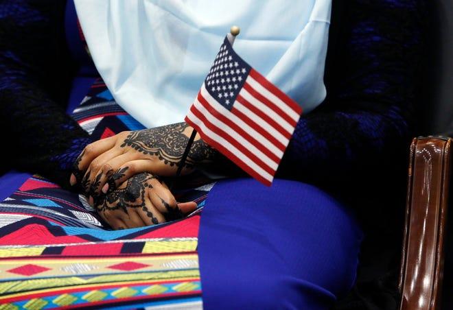 Sadiyo Igal, a native of Somalia, holds a U.S. flag at a 2017 naturalization ceremony in Columbus.