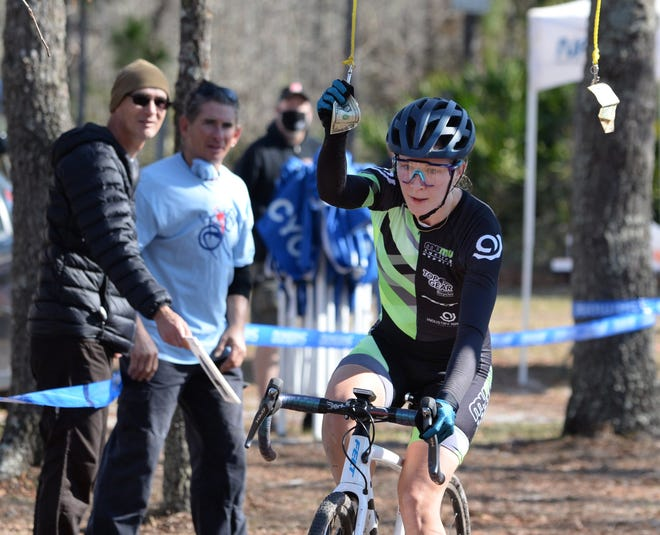 Cyclist Darla Woodall grabs hanging cash, used as a rider incentive, during final laps of the Florida State Cyclocross Championship on Sunday at Ronnie Van Zant Memorial Park in Lake Asbury. Cyclocross is form of bicycle racing featuring wooded trails, grass, steep hills and obstacles requiring the rider to quickly dismount, carry the bike while navigating the obstruction and remount.
