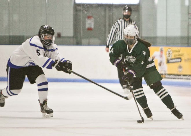 Oakmont/Monty Tech's Kelly Paquet, right, advances the puck past Leominster's Molly Kimball during Saturday's game at Gardner Veterans Arena.