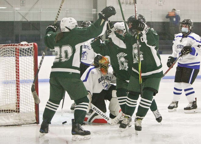 Oakmont/Monty Tech's Ashley Jorge (20) celebrates her goal — the first of the Spartans' season — with teammates Rachel Simkiewicz (middle) and Annaka Gendron during the second period of Saturday's game against the Leominster Blue Devils at Gardner Veterans Arena.
