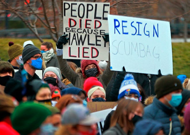 About 300 demonstrators gather after painting a sign in the middle of Broadway Saturday, Jan. 9, 2021 outside the historic Old Courthouse in downtown St. Louis. Speakers called for Sen. Josh Hawley, R-Mo., to resign following a seizure and occupation of the U.S. Capitol in Washington. (Christian Gooden/St. Louis Post-Dispatch via AP)