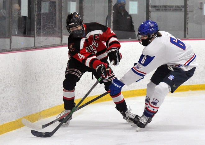 North Quincy's Ben Wines, left, and Quincy's Joseph Hennessey fight for the puck along the boards during boys ice hockey action at the Quincy Youth Arena, Saturday, Jan. 9, 2021.