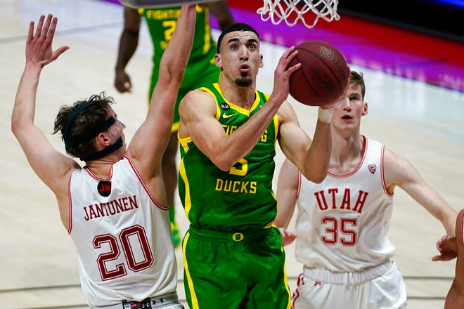 Oregon guard Chris Duarte, center, goes to the basket as Utah's Mikael Jantunen (20) and Branden Carlson (35) defend in the first half on Saturday. (AP Photo/Rick Bowmer)