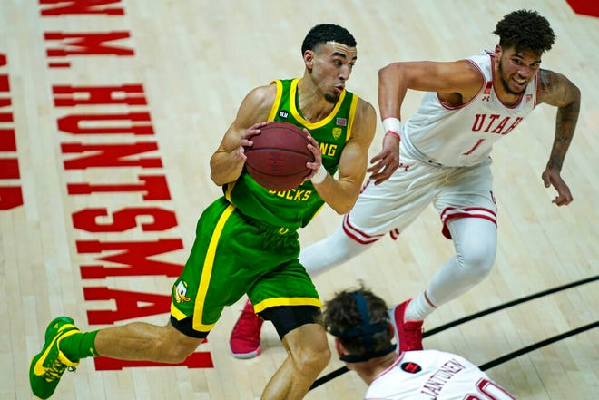 Oregon guard Chris Duarte drives to the basket as Utah forward Timmy Allen (1) defends during the first half on Saturday.