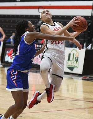McKinley's Nakyah Terrell (right) goes to the hoop as Lake's Serenitee Johnson defends during a Jan. 9, 2021 game at Memorial Field House.