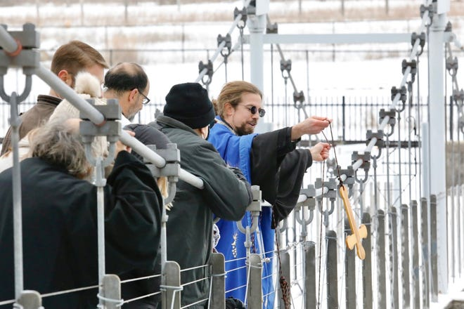 Jonathan Bannon of Christ the Savior Orthodox Church tosses a cross Sunday, Jan. 10, 2021, into Kent Creek behind Tinker Swiss Cottage in Rockford. The act was part of the annual Blessing of the Rock River.