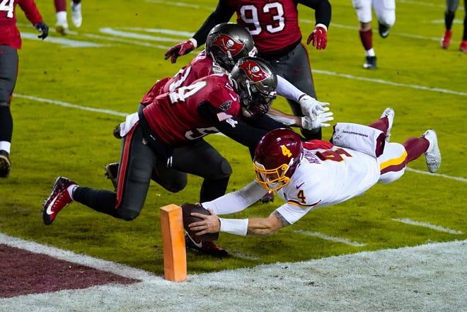 Washington Football Team quarterback Taylor Heinicke (4) dives for a touchdown against Tampa Bay Buccaneers inside linebackers Kevin Minter (51) and Lavonte David (54) during the second half of an NFL wild-card playoff game Saturday, Jan. 9, 2021, in Landover, Md.