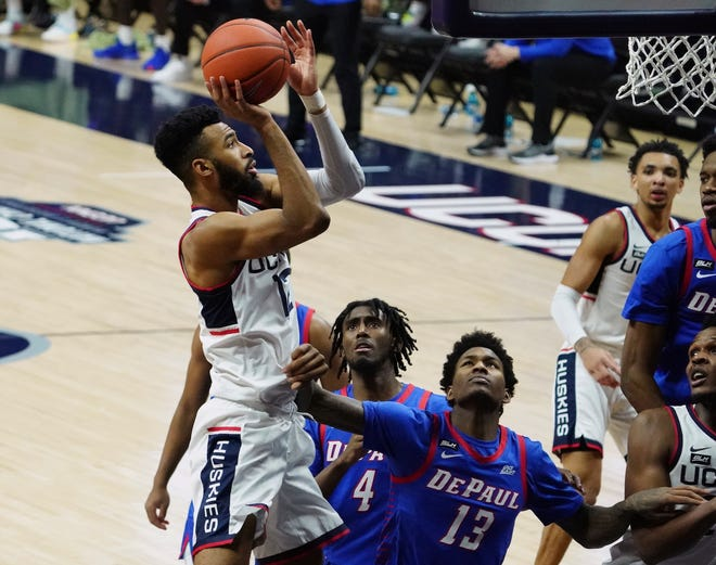 Connecticut forward Tyler Polley (12) drives to the basket against DePaul forward Darious Hall (13) during the Huskies' win Dec. 30, 2020 in Storrs.