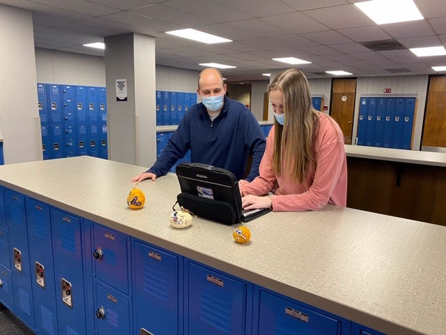Matt Tinsley, left, a teacher and coach at Seaman High School, helps his student, Rylee Hoffer, a freshman, as she looks to expand her small business. Hoffer was inspired to do so after taking Tinsley's intro to business course last semester.