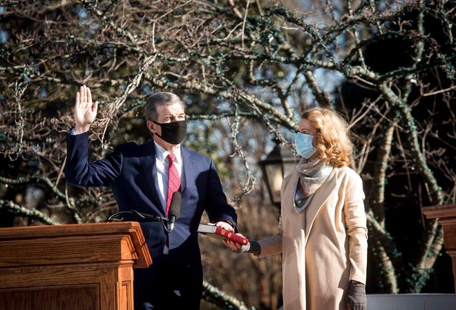Gov. Roy Cooper raises one hand and places his other hand on the Bible held by his wife, Kristin Cooper, during his inauguration for a second term on Saturday, Jan. 9,  2021, in Raleigh, N.C. The in -person ceremony for him and eight other top state elected leaders was truncated due to concerns about COVID-19. (Kate Medley via AP, Pool Photo)