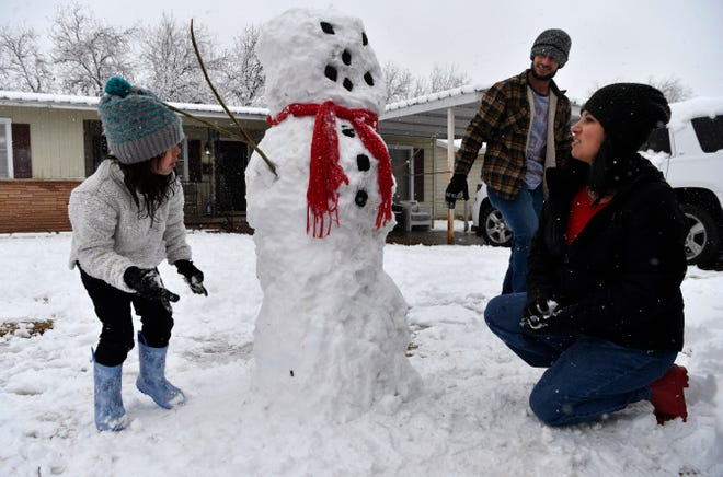 Taylor Young, 5, inspects her handiwork as she builds a snowman with her parents Paul and Brittney during Sunday's morning snowfall in the 2000 block of Woodard Street.