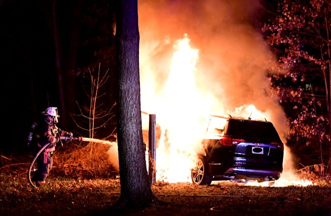 A firefighter works to put out a car fire after it burst into flames when a driver crashed it in Sycamore Township. (The license plate has been blurred.)