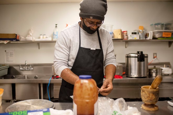 Entrepreneur Juliano Jean-Jules cooks Caribbean cuisine for his pop-up restaurant Island Style BBQ inside a commissary kitchen at Kellogg Arena on Tuesday, Dec. 29, 2020, in Battle Creek.