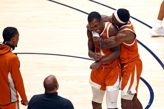 Texas guards Andrew Jones (1) and Courtney Ramey (3) celebrate after Jones scored against West Virginia during the second half.