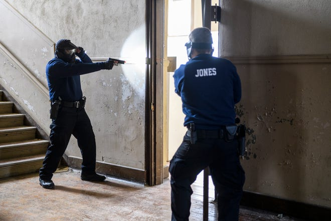 Evansville Police Department recruits John Darakjian, left, and Rayce Jones participate in an active shooter training drill inside an old empty school building run by the Emergency Management Agency on Evansville's West Side, Wednesday afternoon, Jan. 6, 2021. The recruits held up Airsoft guns and flashlights as they cleared each room waiting for trainers to simulate an attack for them to respond to.