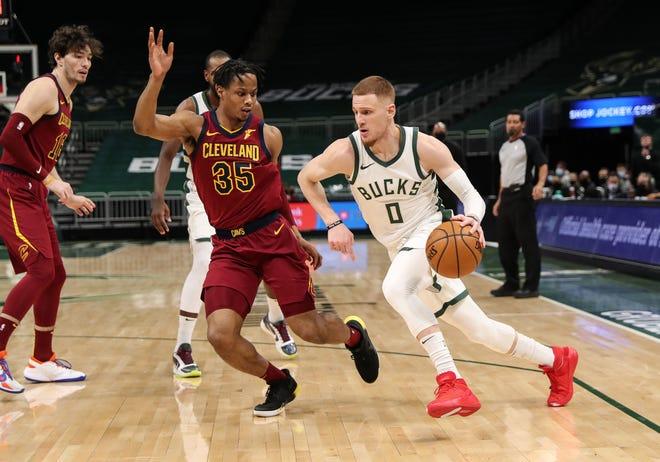 Milwaukee Bucks guard Donte DiVincenzo drives past Cavaliers guard Isaac Okoro during the Bucks 100-90 win Saturday night in Milwaukee. [Nick Monroe/Handout photo USA TODAY Sports]