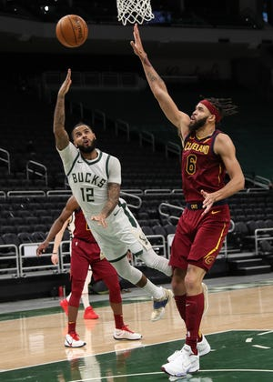 Milwaukee Bucks guard D.J. Augustin tosses up an off-balanced shot by the rim over Cavaliers center JaVale McGee during the Bucks 100-90 win Saturday night in Milwaukee. [USA TODAY Sports]