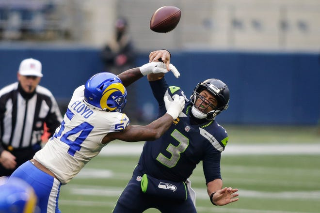 Los Angeles Rams outside linebacker Leonard Floyd (54) knocks the ball away as Seattle Seahawks quarterback Russell Wilson tries to pass during the first half of an NFL wild-card playoff football game, Saturday, Jan. 9, 2021, in Seattle.