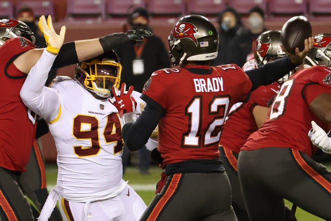 Tampa Bay Buccaneers quarterback Tom Brady passes the ball under pressure from Washington Football Team tackle Daron Payne in the first quarter at FedExField.