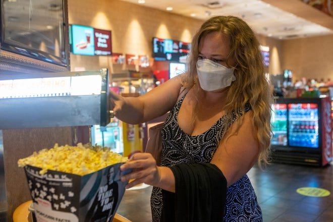 Shiloh Kelley adds butter to her popcorn before heading to a movie inside the Cinemark at Southpark Meadows in August.