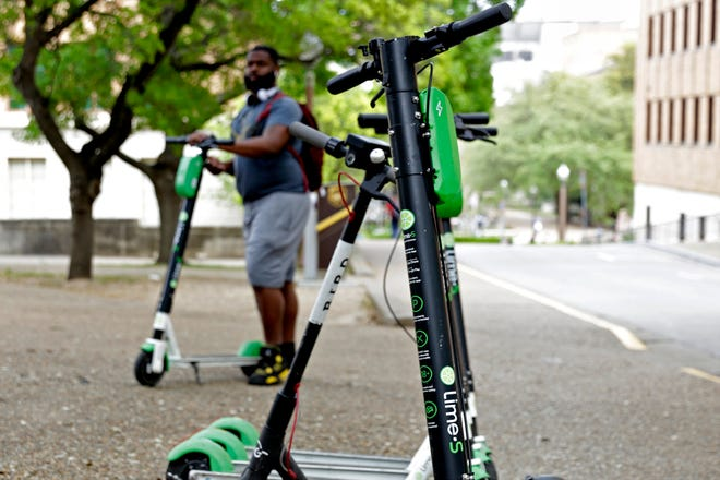 Braun Crenshaw, an employee for Lime, uses scooters to get around in March 2019 in Austin. During its May 25 meeting, the Bastrop City Council approved the first reading of a new city ordinance regulating electric bicycles, bicycles equipped with GPS and motor-assisted scooters.