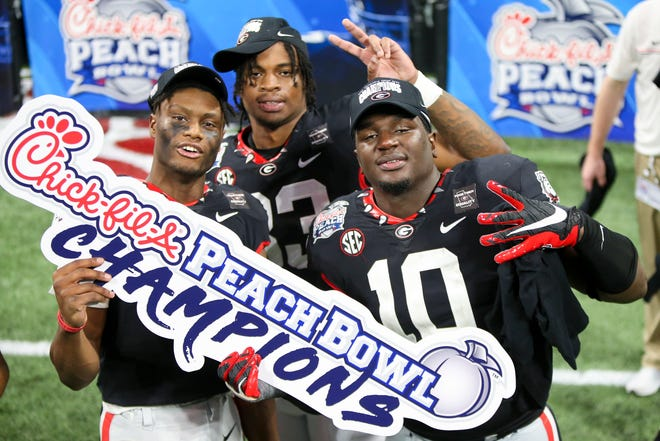 Jan 1, 2021; Atlanta, GA, USA; Georgia Bulldogs wide receiver George Pickens (1) and linebacker Robert Beal Jr. (33) and defensive lineman Malik Herring (10) celebrate after a victory against the Cincinnati Bearcats in the Chick-fil-A Peach Bowl at Mercedes-Benz Stadium. Mandatory Credit: Brett Davis-USA TODAY Sports