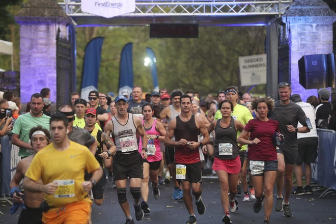 Runners stream through the gates of the starting line for the Akron Children's Hospital Akron Marathon at Stan Hywet Hall & Gardens on Saturday Sept. 28, 2019.