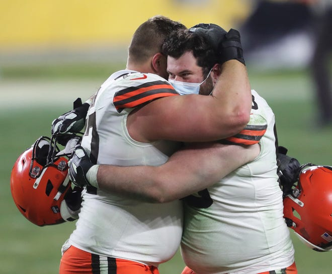 Cleveland Browns offensive tackle Michael Dunn (68) hugs offensive guard Wyatt Teller (77) after beating the Pittsburgh Steelers in an NFL wild-card playoff football game, Sunday, Jan. 10, 2021, in Pittsburgh, Pennsylvania. [Jeff Lange/Beacon Journal]