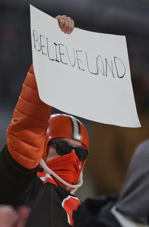 A Browns fan celebrates the team's first playoff win since 1995 after Sunday night's 48-37 win over the Pittsburgh Steelers 48-37. [Jeff Lange/Beacon Journal]