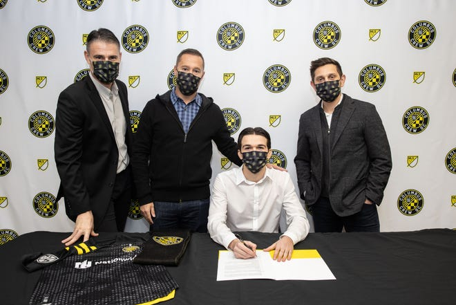 Crew homegrown signee Isaiah Parente, seated, with, from left, team technical director Pat Onstad, coach Caleb Porter and president/general manager Tim Bezbatchenko