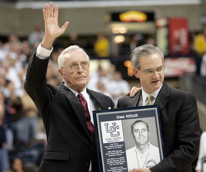 Former University of Connecticut head men's basketball coach Dee Rowe, left, waves to the crowd after he was presented with a plaque by UConn director of athletics Jeff Hathaway at a ceremony honoring former UConn players and coaches in 2007.